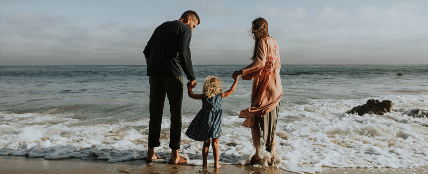 Mother and father standing in the surf holding young daughters hand.